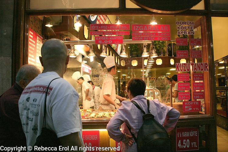 Tourists looking in the window of a restaurant on Istiklal Caddesi, Beyoglu, Istanbul, Turkey