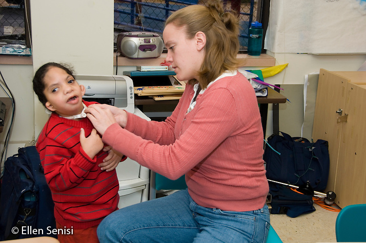 MR / Albany, NY.Langan School at Center for Disability Services .Ungraded private school which serves individuals with multiple disabilities.Teacher puts on child's Passy-Muir valve which helps him speak. Boy: 7, African-American, Pierre Robin syndrome, limited verbal output with expressive and receptive language delays, has Passy Muir valve to redirect air flow to produce speech.MR: Smi24; Ris4.© Ellen B. Senisi