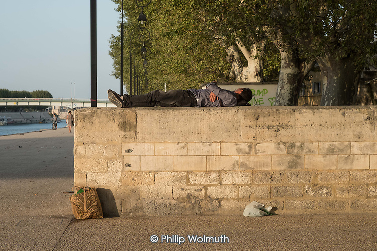 Drunk man sleeping on a wall by the banks of the Rhone, Arles, France.
