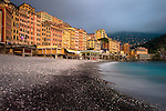 Beach of Camogli with the huge houses at the boardwalk in dramatic light. The hill / Monte di Portofino and the Hotel Cenobio Dei Dogi at the end of the view.