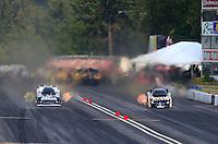 Aug. 2, 2014; Kent, WA, USA; NHRA funny car driver Tim Wilkerson (left) races alongside Tony Pedregon during qualifying for the Northwest Nationals at Pacific Raceways. Mandatory Credit: Mark J. Rebilas-