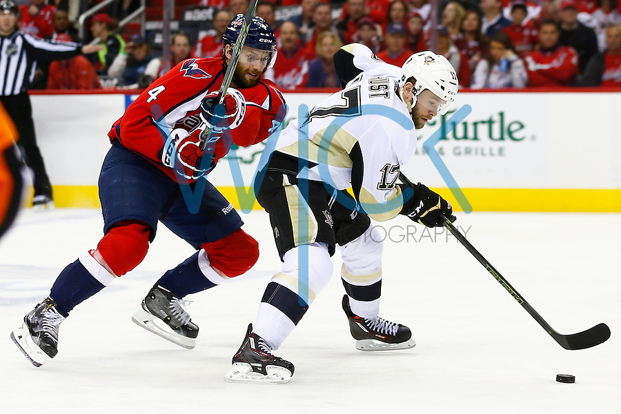 Bryan Rust #17 of the Pittsburgh Penguins carries the puck up the ice in front of Taylor Chorney #4 of the Washington Capitals in the second period during game two of the second round of the Stanley Cup Playoffs at Verizon Center in Washington D.C. on April 30, 2016. (Photo by Jared Wickerham / DKPS)