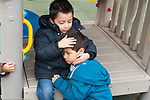 Preschool 3-4 year olds outside playground empathy one boy hugging and comforting another horizontal