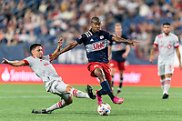 FOXBOROUGH, MA - JULY 7: Mark Delgado #8 of Toronto FC tackles Maciel #13 of New England Revolution during a game between Toronto FC and New England Revolution at Gillette Stadium on July 7, 2021 in Foxborough, Massachusetts.