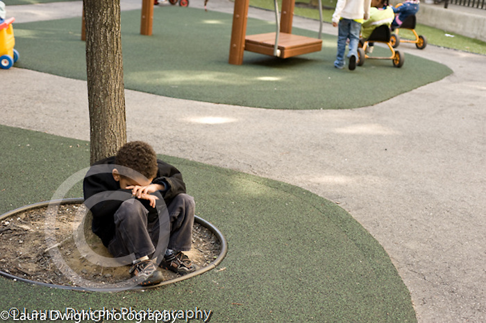 Preschool backyard playground children playing in early spring ages 3-5 New York City isolated unhappy boy sitting alone at base of tree resting head on hands vertical