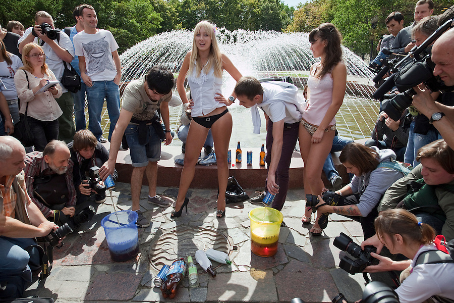 """Moscow Russia, 04/08/2011..A group of young women calling themselves the Medvedev Girls demonstrate in central Moscow in support of Russian President Dmitri Medvedev in response to similar recent actions supporting Vladimir Putin. Under the slogan """"Choose beer or us"""" the women invited members of the public strolling on Pushkin Square to pour their cans of beer into buckets and as the level of donated beer rose three of the women stripped to bikinis."""