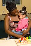 preschool 2-3 year olds separation beginning of school day female teacher comforting sad girl