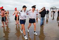 Traditionele Nieuwjaarsduik in Scheveningen. Agenten in minirok en korte broek