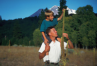 Father and son examining wildflower, Mt. Shasta in background, California