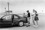 Decatur, Texas, USA 1999. A young family wait for assistance in the parking lot of a petrol station. They have been involved in a minor traffic accident.