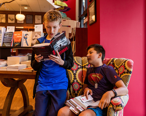"""July 26, 2017. Raleigh, North Carolina.<br /> <br /> (left to right) Collin Aherne and Noah deVries check out Alan Gratz's new book """"Refugee"""" before the signing event begins. <br /> <br /> Author Alan Gratz spoke about and signed his new book """"Refugee"""" at Quail Ridge Books. The young adult fiction novel contrasts the stories of three refugees from different time periods, a Jewish boy in 1930's Germany , a Cuban girl in 1994 and a Syrian boy in 2015."""