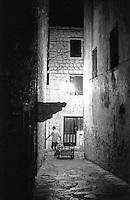 """Stari Grad (Cittavecchia di Lesina), cittadina sull'isola di Hvar tra le più antiche d'Europa. Un uomo con un carretto in un vicolo --- Stari Grad (""""old town"""") on the island of Hvar, one of the oldest towns in Europe. A man with a cart in an alley"""