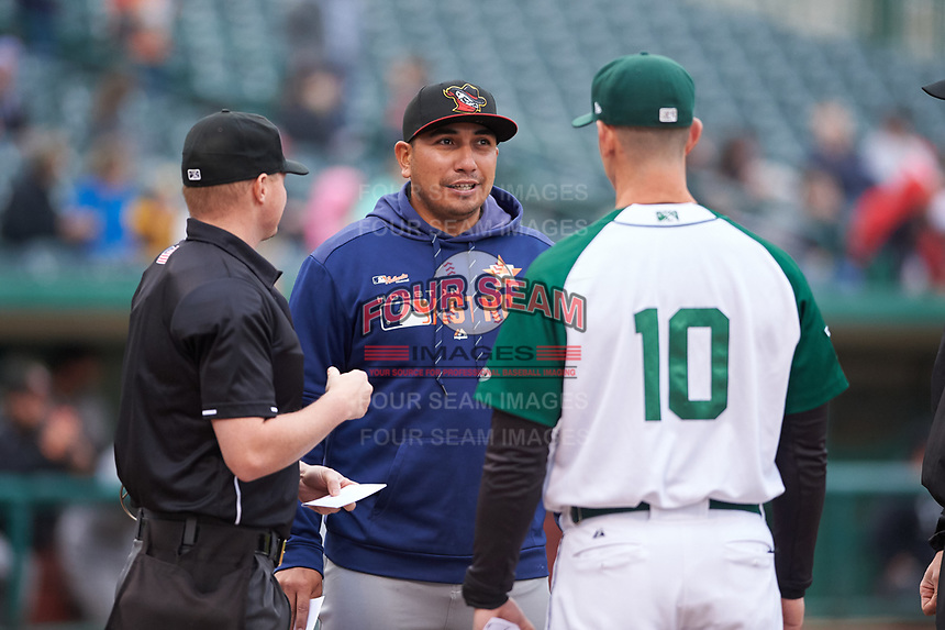 Quad Cities River Bandits manager Ray Hernandez (12) during a pregame meeting with umpire Lance Seilhamer and Fort Wayne TinCaps manager Anthony Contreras (10) before a Midwest League game at Parkview Field on May 3, 2019 in Fort Wayne, Indiana. Quad Cities defeated Fort Wayne 4-3. (Zachary Lucy/Four Seam Images)