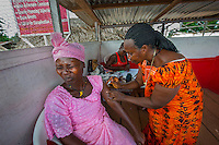 AWright_LIB_003601.jpg<br /> Liberia<br /> Patience Flomo (left) winces as she receives her three-month Depo-Provera contraceptive shot from Theresa Gloli (right), a trained midwife and nurse. Theresa manages a family planning health clinic at the market in Gbarnga every Friday, the busiest day of the week.