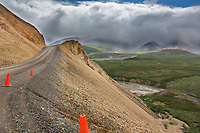 The narrow Denali park road is marked by orange cones in the Polychrome mountains of Denali National Park, interior, Alaska.