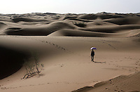 A tourist walks off into the sand dunes of the Shapotou Tengger desert resort near the city of Zhongwei, in Ningxia Province. The park was established next to a Chinese Academy of Sciences research station, involved in studies investigating desertification control measures. The Shapotou park draws thousands of visitors who ride camels, do sand sliding and take boat rides on the nearby Yellow River.