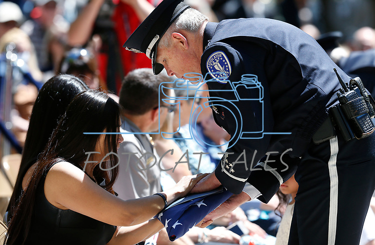 Nevada Legislative Police Chief John Drew presents an American flag to Arlyn Eng, the widow of Las Vegas Department of Public Safety Corrections Officer Kyle Eng, who died in the line of duty in 2018. Eng was one of two officers added to the memorial during the 22nd annual Nevada Law Enforcement Officers Memorial ceremony in Carson City, Nev., on Thursday, May 2, 2019. <br /> Photo by Cathleen Allison/Nevada Momentum