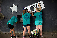 """Members create a mural under a train bridge during """"Circle the City with Service,"""" the Kiwanis Circle K International's 2015 Large Scale Service Project, on Wednesday, June 24, 2015, in Indianapolis. (Photo by James Brosher)"""