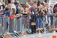 Pictured: Gareth Thomas is embraced by his husband Stephen minutes after he started his marathon run. Sunday 15 September 2019<br /> Re: Ironman triathlon event in Tenby, Wales, UK.