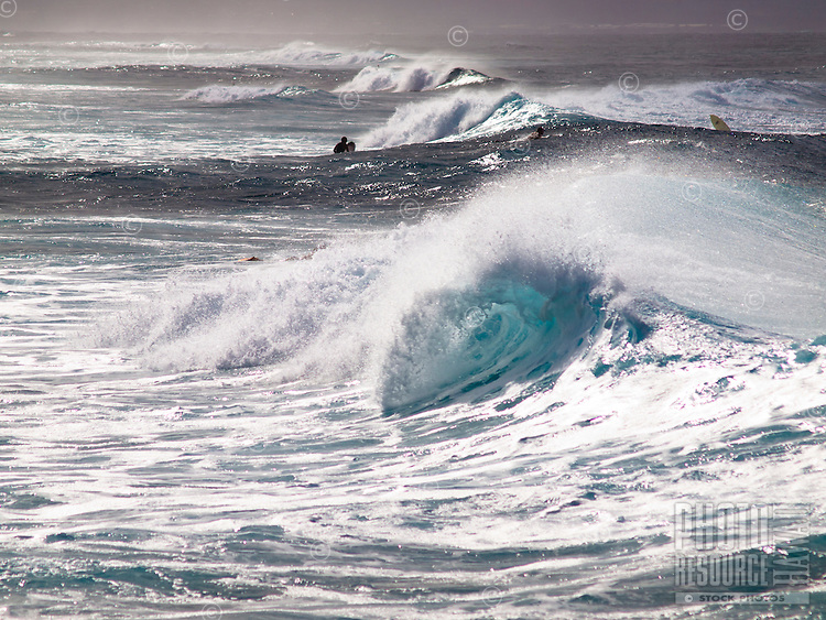 Waves crash at Maui's Ho'okipa Beach as surfers make their way out to ride.