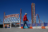 BROOKLYN - NEW YORK - APRIL 08: A woman walks at Coney Island on April 08, 2021 in New York. After 18 months of closure due to the Coronavirus pandemic, Coney Island parks will welcome visitors taking safety restrictions including physical distancing through reduced capacity. (Photo by John Smith/VIEWpress)
