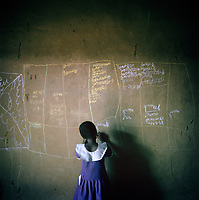 Aichadou, six, practises writing the days of the week in French with chalk on the wall of the small home she shares with her pregnant mother and four year old brother Ibrahim. <br /> <br /> Most IDPs in this camp do not have ID cards, they were lost or destroyed in the conflict. Securing a new ID card is very difficult, often needing a birth certificate from your village of origin, because of the conflict some of these villages no longer exist. Without an ID card, children like Aichadou can't apply for a place at school.