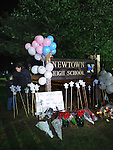 NEWTOWN, CT - 16 December 2012-121612EC03--    Vedael Morales of Bridgeport and her son Jonathan, 6, place balloons at the entrance of Newtown High School before the interfaith vigil Sunday night.  Morales says her it was her son's idea to show up at the memorial.  Erin Covey Republican-American.