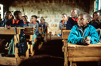 Kenya. Rift Valley Province. Mwenja. Primary school. Classroom. Students, girls and boys, listens to their teacher's lesson.The arms are laid on a wood desk . The pupils are wearing a green and orange uniform. © 2004 Didier Ruef