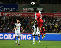Pictured: Mid air battle for a header between Wilfried Bony of Swansea and Lucas Leiva of Liverpool.<br /> Monday 16 September 2013<br /> Re: Barclay's Premier League, Swansea City FC v Liverpool at the Liberty Stadium, south Wales.