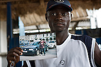 Atta holds a picture of himself next to a car which he sent home to his family when he tried to travel overland to Europe, in order to keep the impression he was doing well. However, only a minority of the migrants manage to cross into Europe proving his trip to be unsuccessful.