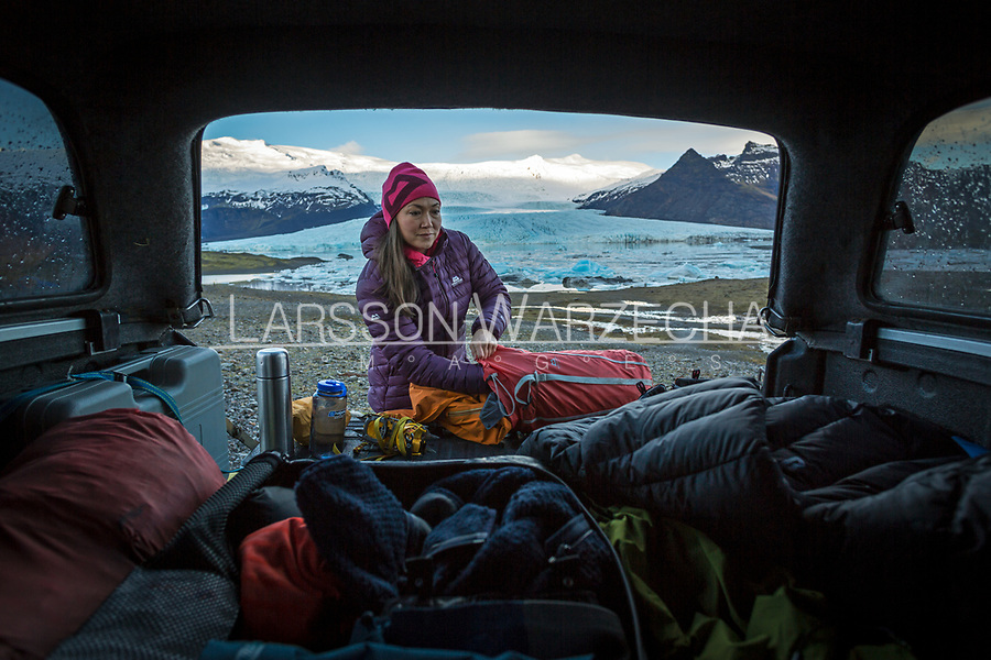 Female hiker packs her backpack from a tailgate of 4x4 vehicle with mountains and glaciers in the background, Iceland