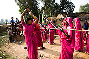 The 47-year-old leader of the Pink Gang, Sampat Pal Devi is seen teaching lathi fighting skills to the members of the pink gang. A fiesty woman, barely educated, impoverished mother of five, Sampat Pal Devi has emerged as a messianic figure in the region. Sampath Devi began to work as a government health worker, but she quit soon after because her job was not satisfying enough. She always wanted to work for the poor and not for herself. Taking up issues while being a government worker was difficult, so she decided to quit the job and work for the rights of people...Amidst the gloom of extreme poverty, it's the colour of pink that's calling the shots in this dusty region of Bundelkhand, one of the poorest parts of one of India's northern and most populous states, Uttar Pradesh in India. A gang of vigilantes, called the Gulabi Gang (pink gang) - its 10,000 strong women members wear only pink sarees - is taking up lathi (traditional Indian cudgel) against domestic violence and corruption.