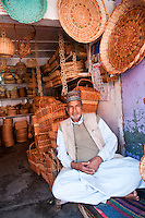 Smiling basket vendor in front of his shop stuffed with wares, Hazratbal area, Srinagar, Kashmir, India.