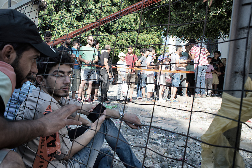Migrants queue at the police station for their permit to travel to Athens. The  wait is often long, causing  tensions to run high on occasion resulting in fights.  Kos, Greece. Sept. 6, 2015
