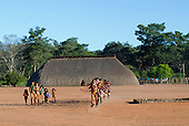 Xingu Indigenous Park, Mato Grosso State, Brazil. Aldeia Waura; a ceremonial dance in front of the House of the Flutes in honour of a recently deceased elder passing the grave (right hand side).