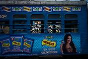 A Calcutta Tramways Company's Tram rides past sculptors preparing Hindu Goddess idols in Kumhartuli in Kolkata, West Bengal, India