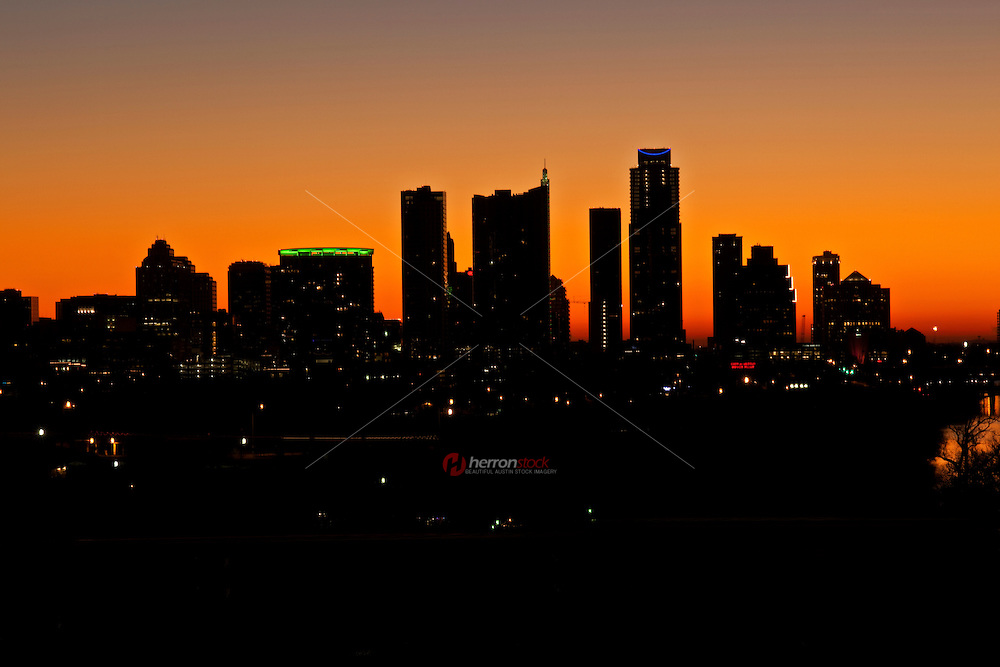 A bright, vivid orange morning sunrise engulfs the city skyline of Austin Texas looking beside the Lake Austin, Colorado River.