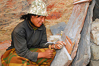 Young Tibetan stone carver chisels a mani, or prayer, stone on the Lingkhor pilgrim circuit as it ascends Chagpo Ri mountain, Lhasa, Tibet, China.