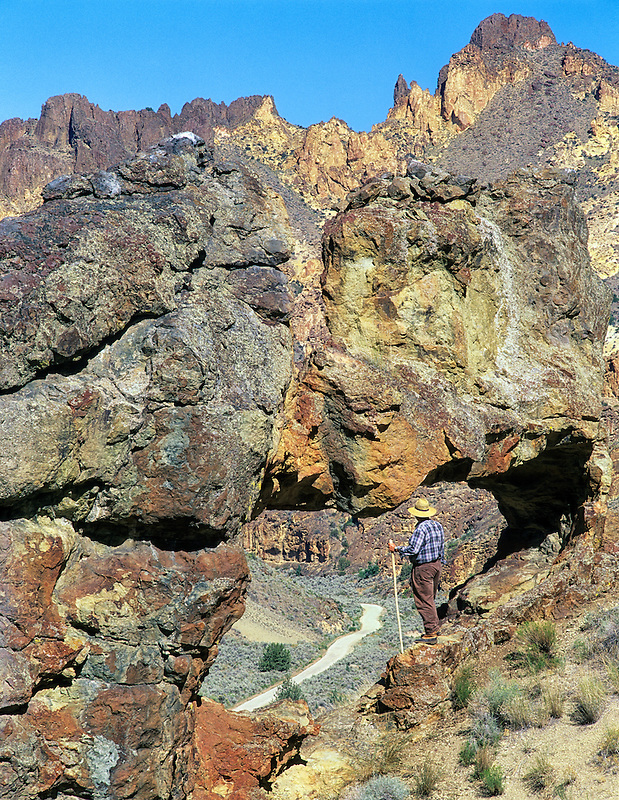 Hiker viewing road in Leslie Gulch through rock arch. Oregon.