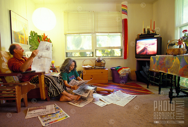 Multi-ethnic couple reading the newspaper on a Sunday morning, with the television on in the background, Kalihi Valley, Oahu