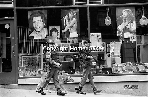 Armed British soldiers with sniffer dog, on patrol in Derry, Londonderry, Northern Ireland .  during the Troubles 1970s UK 1979.