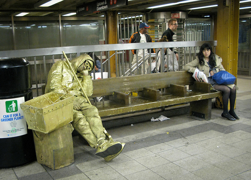 Gold street performer snoozes while waiting for New York city subway.