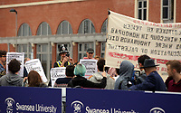 Pictured: A police officer takes a picture of the anti-Hillary Clinton protesters at Swansea University Bay Campus. Saturday 14 October 2017<br /> Re: Hillary Clinton, the former US secretary of state and 2016 American presidential candidate will be presented with an honorary doctorate during a ceremony at Swansea University's Bay Campus in Wales, UK, to recognise her commitment to promoting the rights of families and children around the world.<br /> Mrs Clinton's great grandparents were from south Wales.