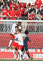 Jeremy Hall #17 and Casey Townsend #7 of the University of Maryland congratulate Omar Gonzalez #4 after he scored the first goal during an NCAA championship round of sixteen soccer match against the University of California at Ludwig Field, on November 29, 2008 in College Park, Maryland. The match was won by Maryland 2-1