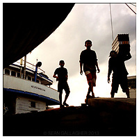Workers load and unload good off of a boat in the port area of central Jakarta, Indonesia.