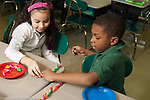 Education Elementary school Grade 1 mathematics hands on learning boy and girl lining up and counting colored plastic dinosaurs horizontal