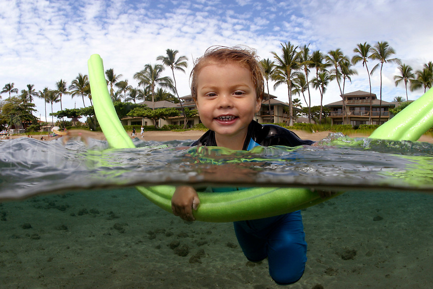 This young toddler (MR) is just getting his feet wet off Maui, Hawaii.  Palm trees can be seen in the background.