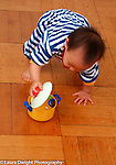 10 month old baby girl Piaget object permanence opening pot in which toy is hidden vertical
