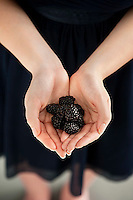 Woman with a handful freshly picked blackberries