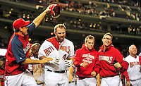 28 September 2010: Washington Nationals' first baseman Adam Dunn has his helmet removed by Ryan Zimmerman as he is surrounded and congratulated by teammates after hitting a walk-off solo home run in the bottom of the 9th inning against the Philadelphia Phillies at Nationals Park in Washington, DC. The Nationals defeated the Phillies 2-1 to even up their 3-game series one game apiece. Mandatory Credit: Ed Wolfstein Photo